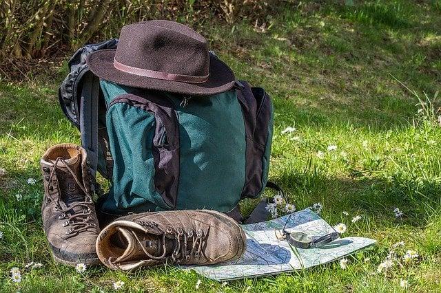 Regalo per amanti del trekking, scarponi, zaino, bussola e mappa su prato