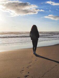Camminata meditativa, donna cammina sulla spiaggia