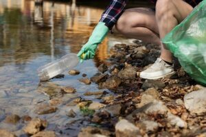 Plogging, ragazza raccoglie rifiuti da un torrente
